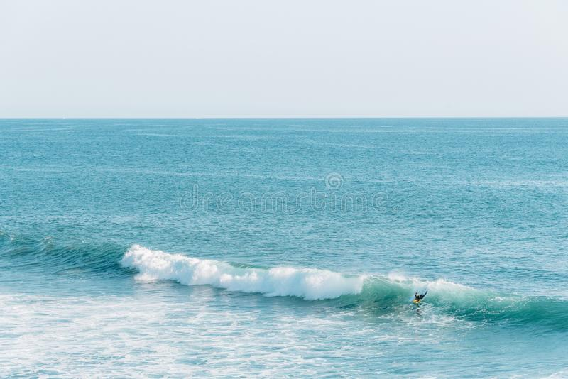 Waves and surfer in the Pacific Ocean, in Laguna Beach, Orange County, California royalty free stock photos