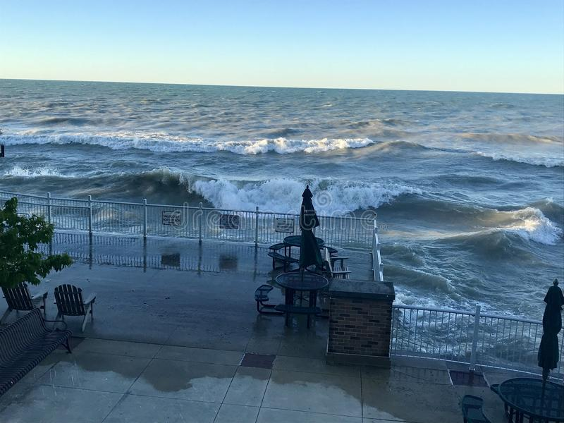 Lake Michigan gets angry. Waves swell on the Illinois side of Lake Michigan, crashing onto the beach and over railings royalty free stock images