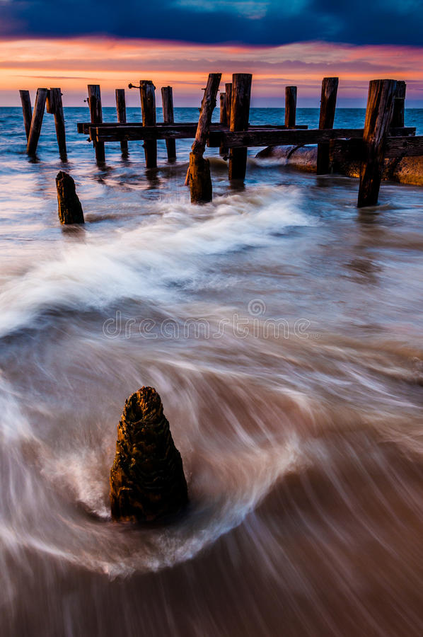 Waves swirl around pier pilings in the Delaware Bay at sunset, s. Een from Sunset Beach, Cape May, New Jersey stock image