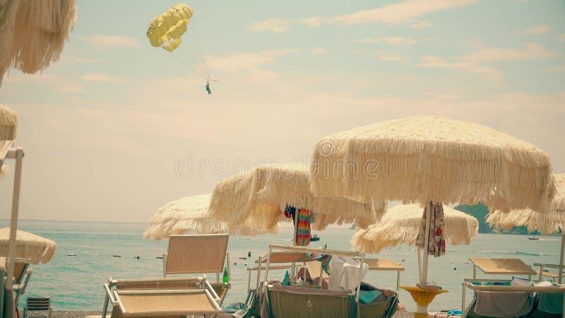 Waving beach umbrellas and distand parasailing parachute at sea stock image