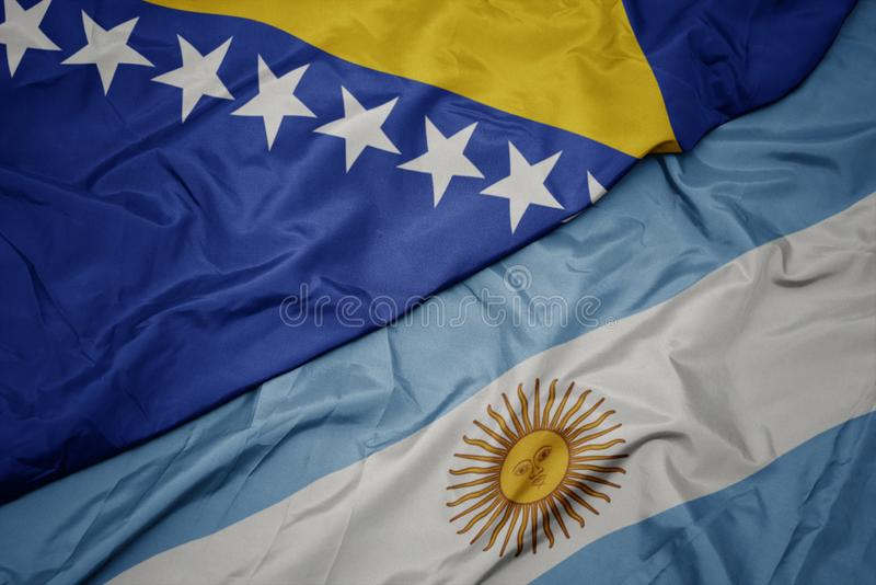 Waving colorful flag of argentina and national flag of bosnia and herzegovina. Macro stock photography