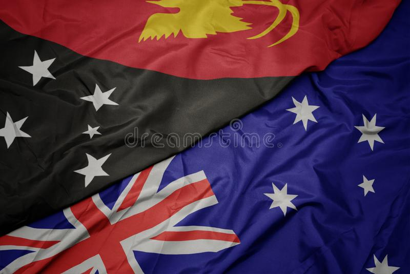 Waving colorful flag of australia and national flag of Papua New Guinea. Macro stock photos