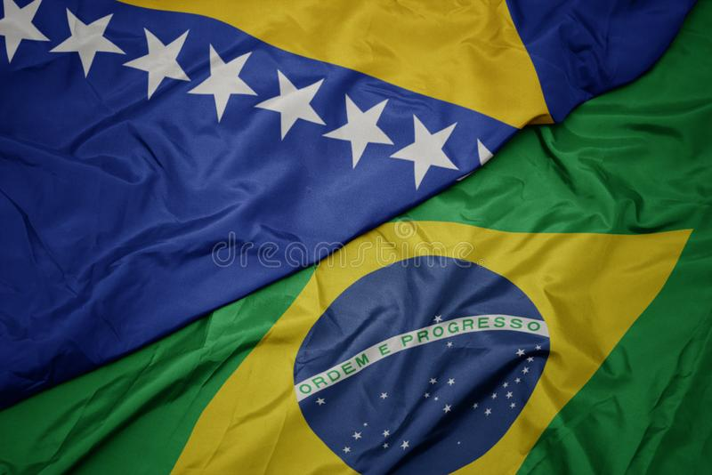 Waving colorful flag of brazil and national flag of bosnia and herzegovina. Macro stock images