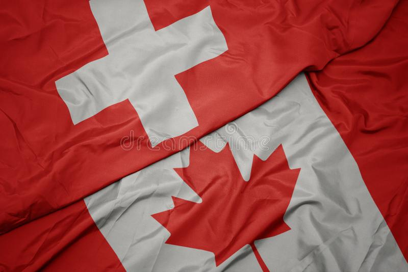 Waving colorful flag of canada and national flag of switzerland. Macro stock images