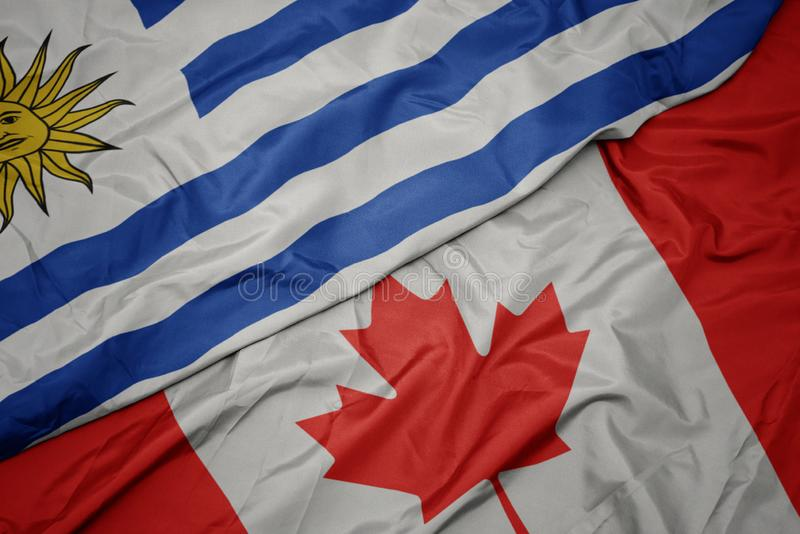 Waving colorful flag of canada and national flag of uruguay. Macro stock photography
