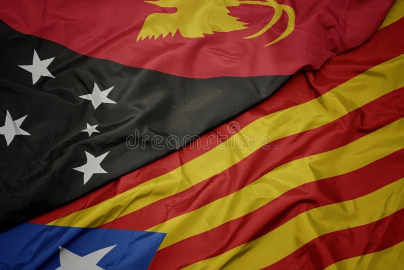 Waving colorful flag of catalonia and national flag of Papua New Guinea. Macro stock photo