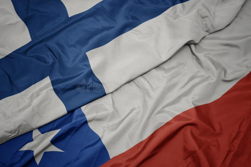Waving colorful flag of chile and national flag of finland. Macro stock photography