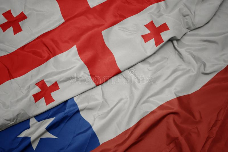 Waving colorful flag of chile and national flag of georgia. Macro stock image