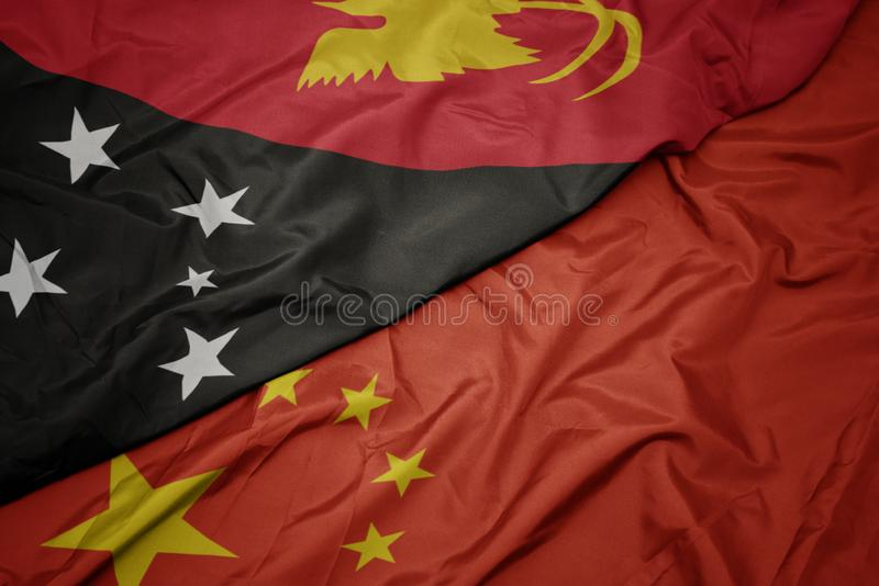 Waving colorful flag of china and national flag of Papua New Guinea. Macro royalty free stock image
