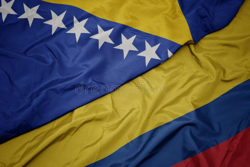 Waving colorful flag of colombia and national flag of bosnia and herzegovina. Macro stock photos
