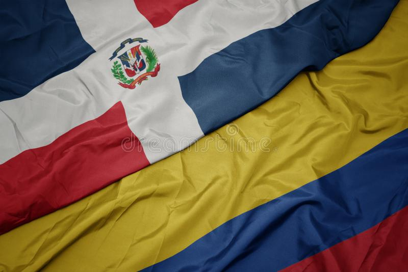 Waving colorful flag of colombia and national flag of dominican republic. Macro royalty free stock image