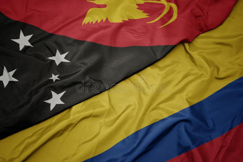 Waving colorful flag of colombia and national flag of Papua New Guinea. Macro royalty free stock image