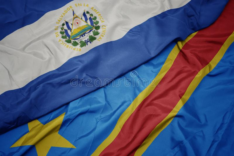 Waving colorful flag of democratic republic of the congo and national flag of el salvador. Macro royalty free stock photo