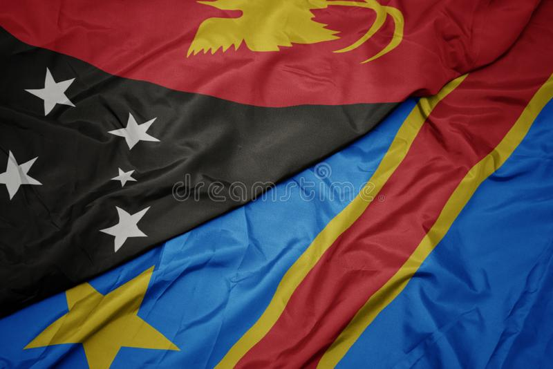 Waving colorful flag of democratic republic of the congo and national flag of Papua New Guinea. Macro stock photo