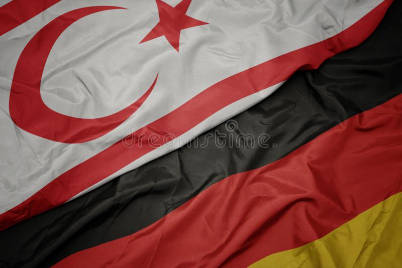Waving colorful flag of germany and national flag of northern cyprus. Macro stock photos
