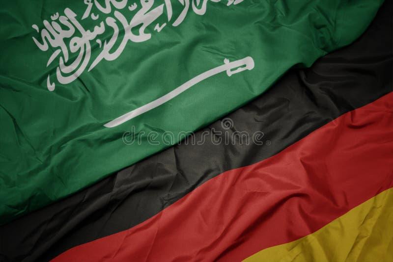 Waving colorful flag of germany and national flag of saudi arabia. Macro royalty free stock photo
