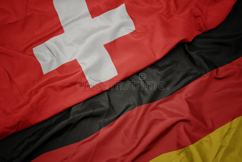 Waving colorful flag of germany and national flag of switzerland. Macro royalty free stock photos
