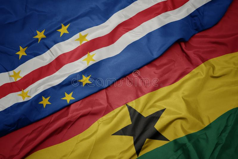 Waving colorful flag of ghana and national flag of cape verde. Macro royalty free stock photography