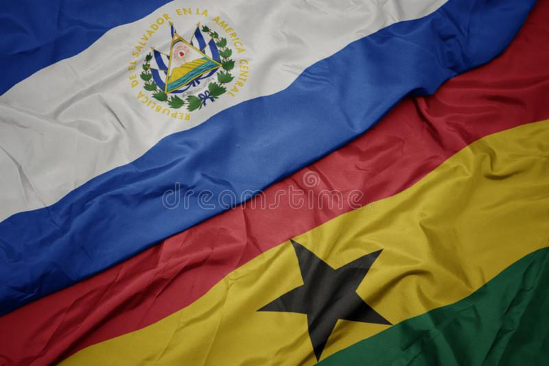 Waving colorful flag of ghana and national flag of el salvador. Macro stock images