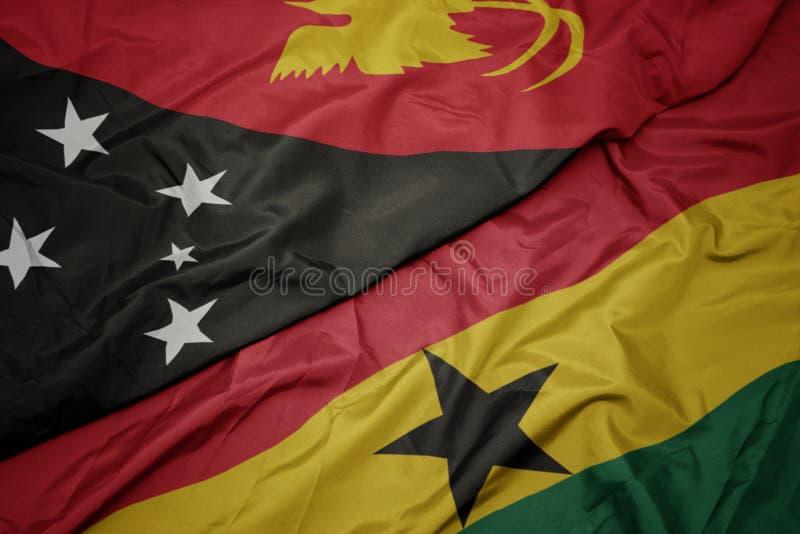 Waving colorful flag of ghana and national flag of Papua New Guinea. Macro stock photo