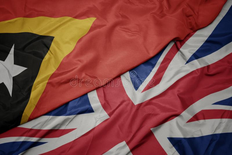 Waving colorful flag of great britain and national flag of east timor. Macro stock photography
