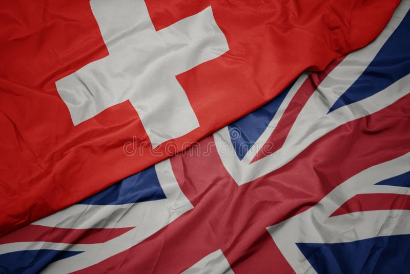 Waving colorful flag of great britain and national flag of switzerland. Macro stock image