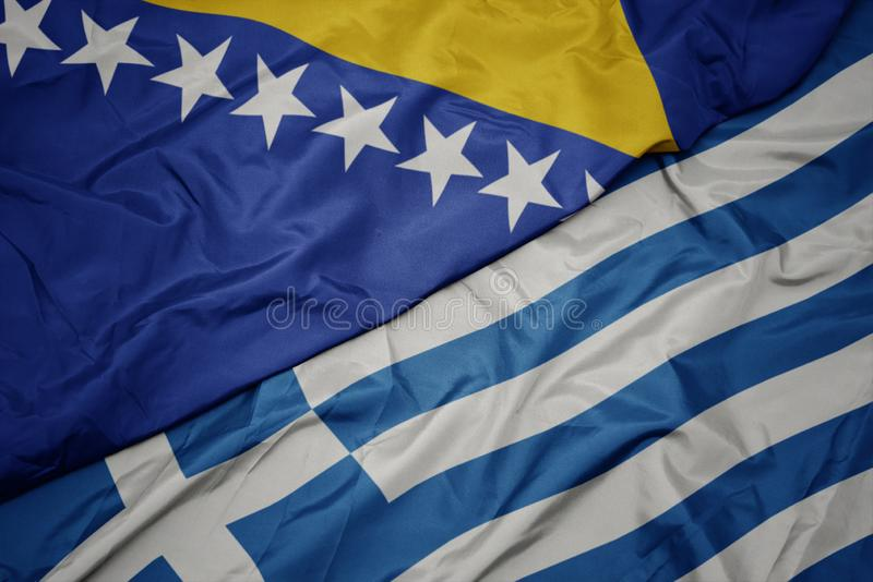 Waving colorful flag of greece and national flag of bosnia and herzegovina. Macro stock image