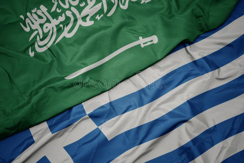 Waving colorful flag of greece and national flag of saudi arabia. Macro stock image
