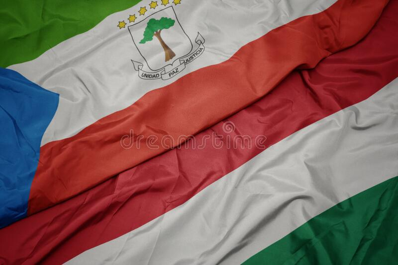 Waving colorful flag of hungary and national flag of equatorial guinea. Macro stock photos