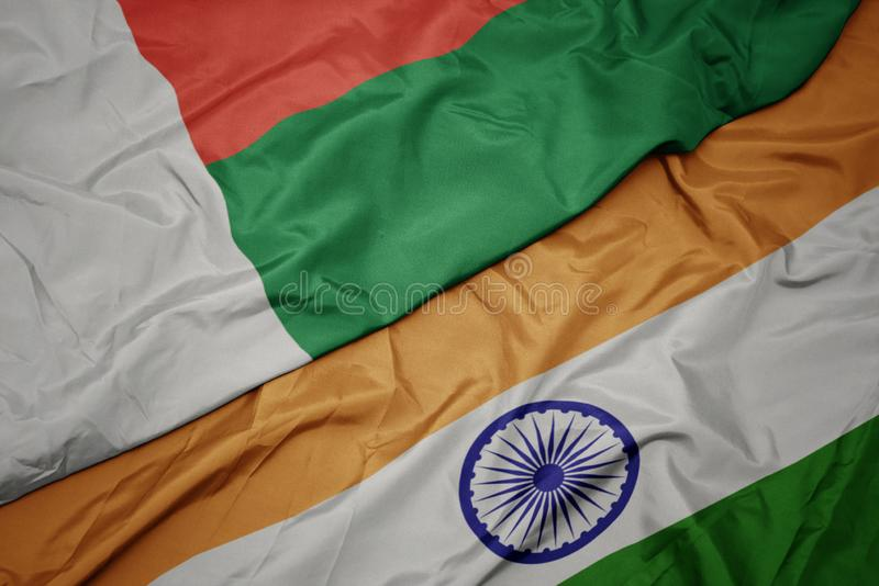 waving colorful flag of india and national flag of madagascar royalty free stock images