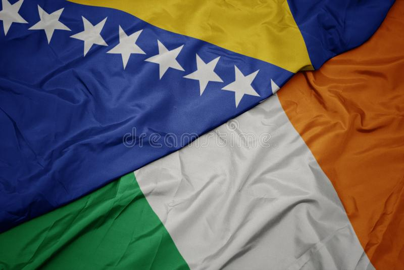 Waving colorful flag of ireland and national flag of bosnia and herzegovina. Macro stock photos