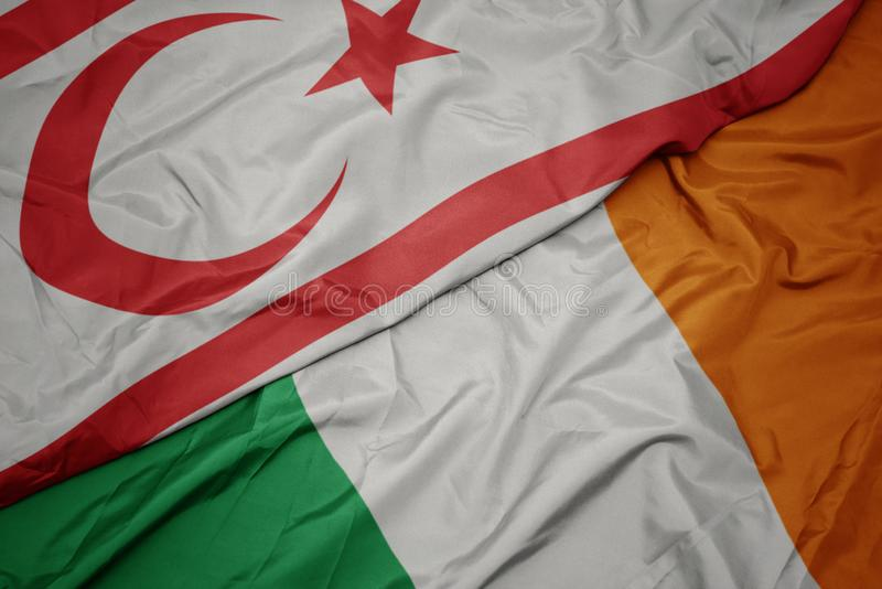 Waving colorful flag of ireland and national flag of northern cyprus. Macro stock image