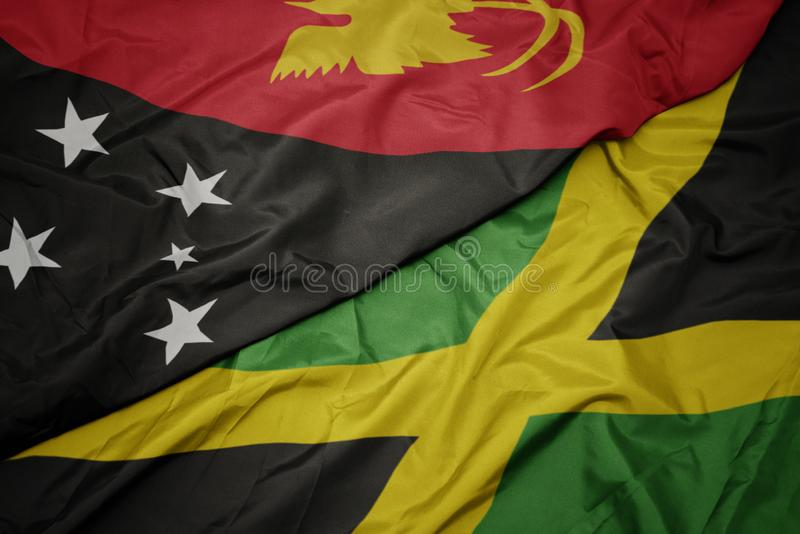 Waving colorful flag of jamaica and national flag of Papua New Guinea. Macro stock photography