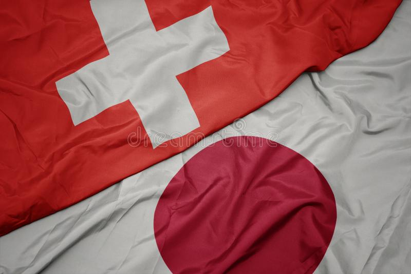 Waving colorful flag of japan and national flag of switzerland. Macro stock images