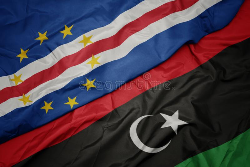 Waving colorful flag of libya and national flag of cape verde. Macro stock image