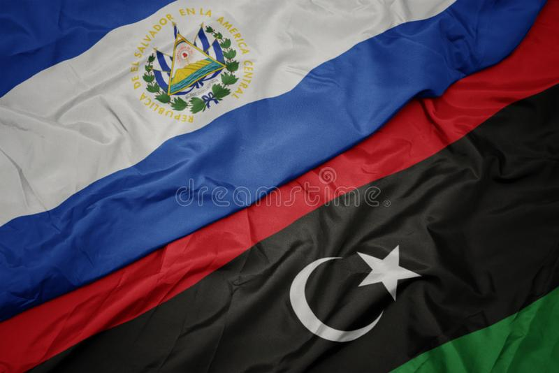 Waving colorful flag of libya and national flag of el salvador. Macro royalty free stock image