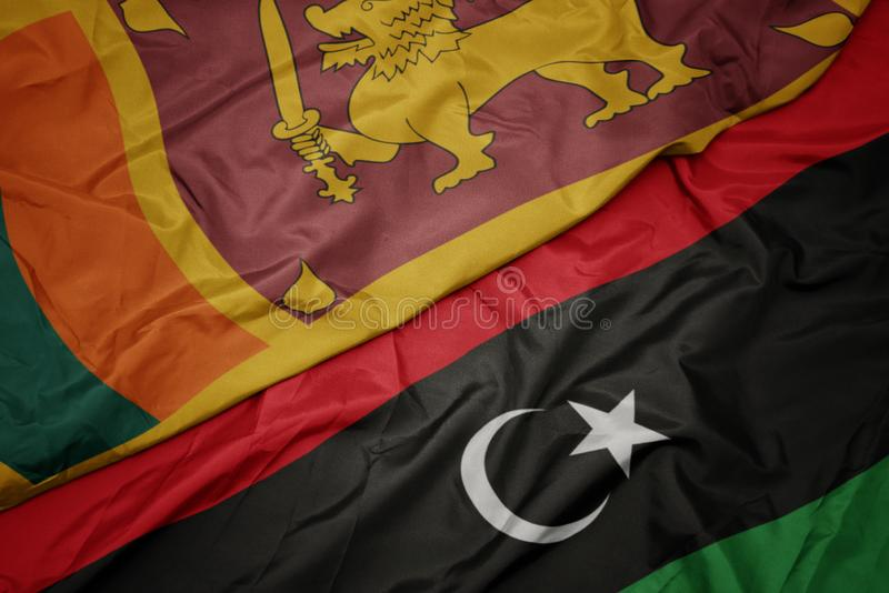 Waving colorful flag of libya and national flag of sri lanka. Macro royalty free stock photos