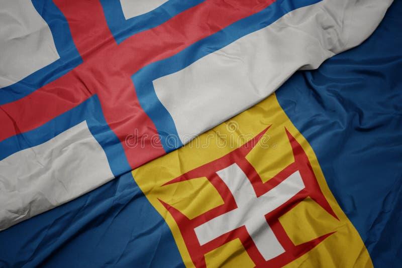Waving colorful flag of madeira and national flag of faroe islands. Macro royalty free stock photos