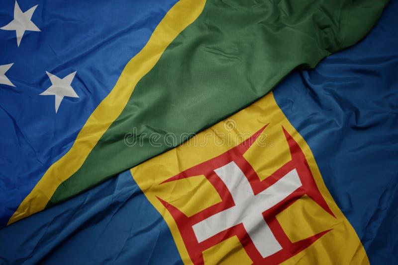 Waving colorful flag of madeira and national flag of Solomon Islands. Macro stock image