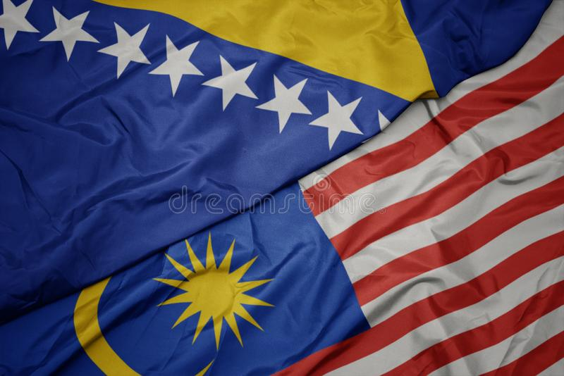 Waving colorful flag of malaysia and national flag of bosnia and herzegovina. Macro stock photos