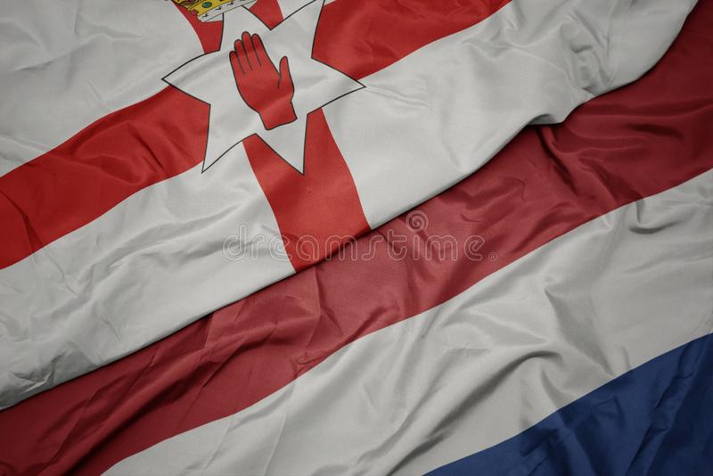 Waving colorful flag of netherlands and national flag of northern ireland. Macro royalty free stock photography