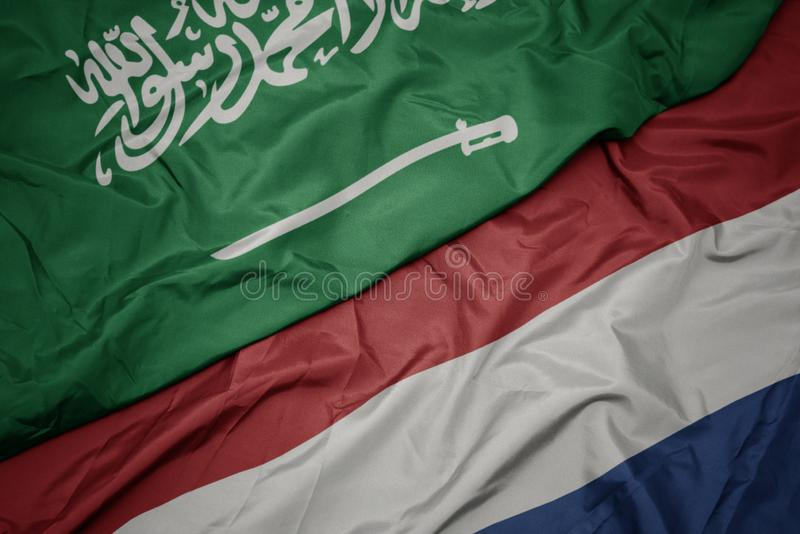 Waving colorful flag of netherlands and national flag of saudi arabia. Macro royalty free stock images