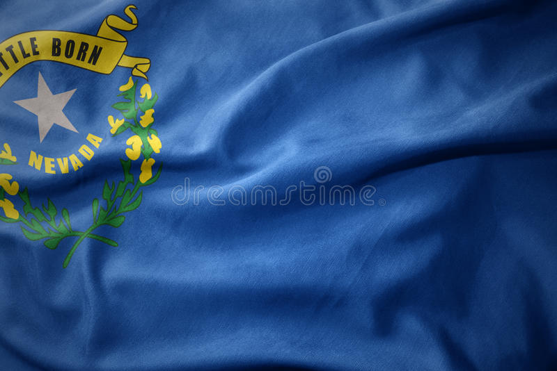 Waving colorful flag of nevada state. stock photos