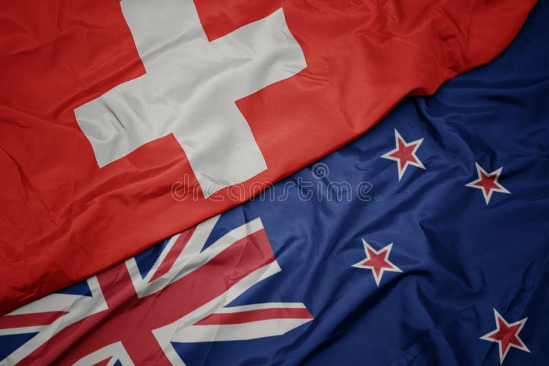 Waving colorful flag of new zealand and national flag of switzerland. Macro stock photos