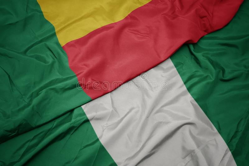 Waving colorful flag of nigeria and national flag of benin. Macro stock photos