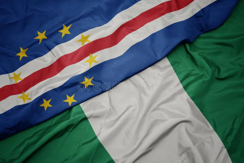 Waving colorful flag of nigeria and national flag of cape verde. Macro stock photography