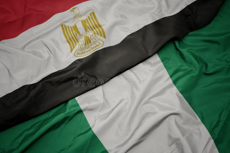 Waving colorful flag of nigeria and national flag of egypt. Macro royalty free stock photography