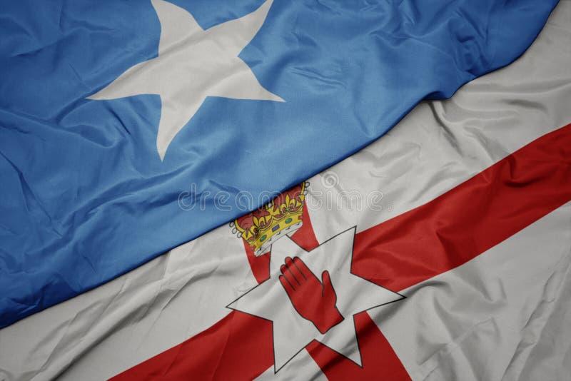 waving colorful flag of northern ireland and national flag of somalia stock image