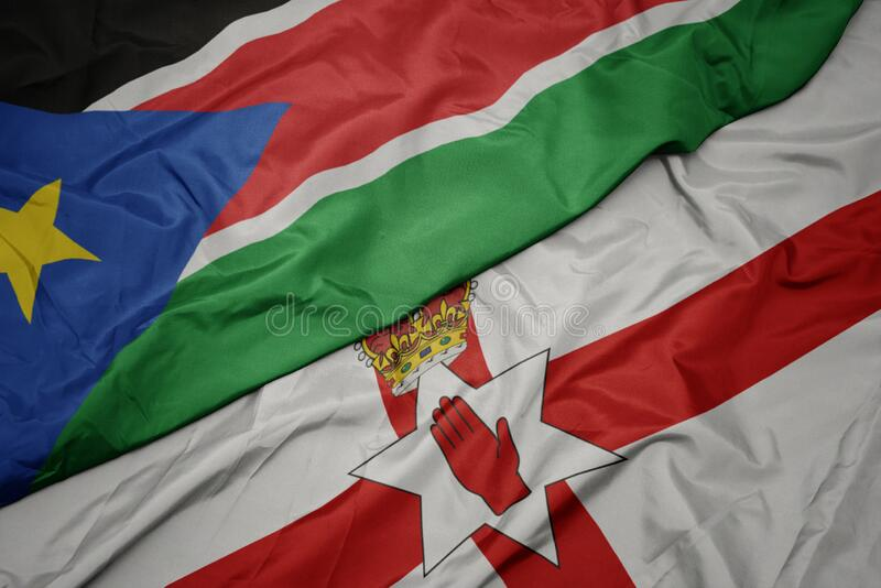 waving colorful flag of northern ireland and national flag of south sudan royalty free stock images