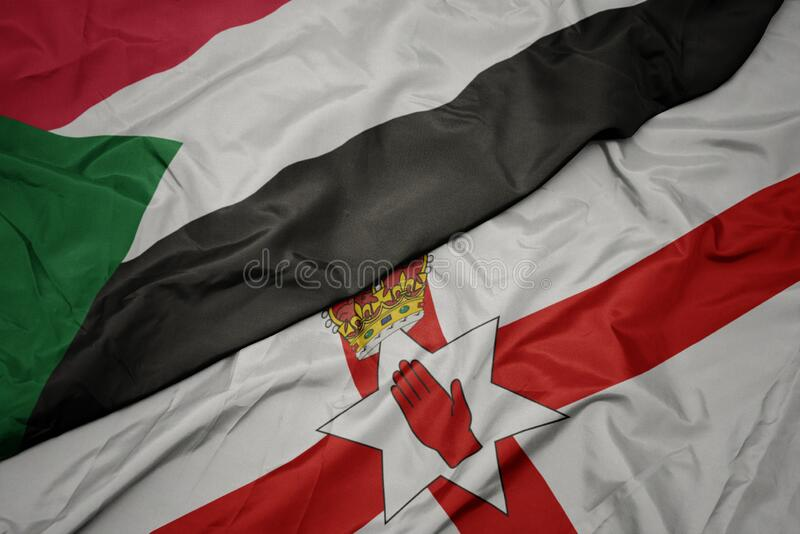 waving colorful flag of northern ireland and national flag of sudan stock images